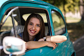 istock Smiling female driver in vintage car looking at camera 1216182076