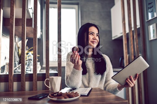 Smiling Female Eating Breakfast And Organizing Day With Clipboard And Digital Tablet