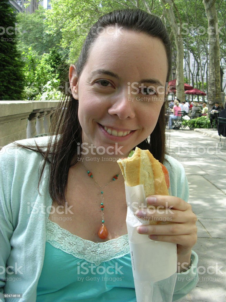 Smiling Female Eating Sandwich royalty-free stock photo