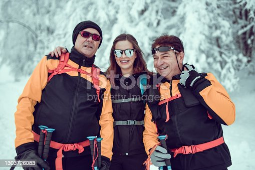 istock Smiling Female Embracing Senior Hikers During Snow Mountaineering 1303726083
