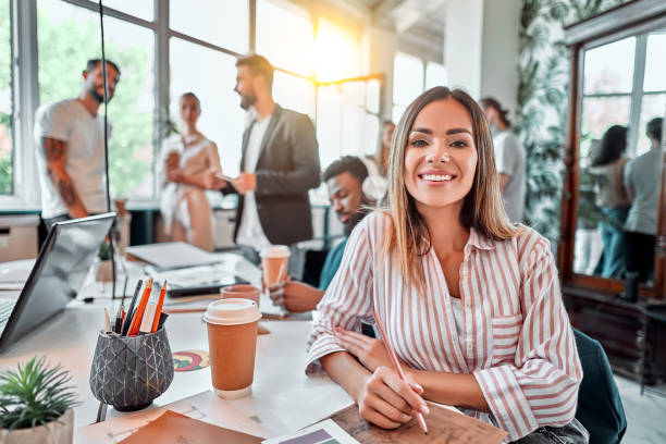 Smiling female employee sit in coworking space and working on the project stock photo