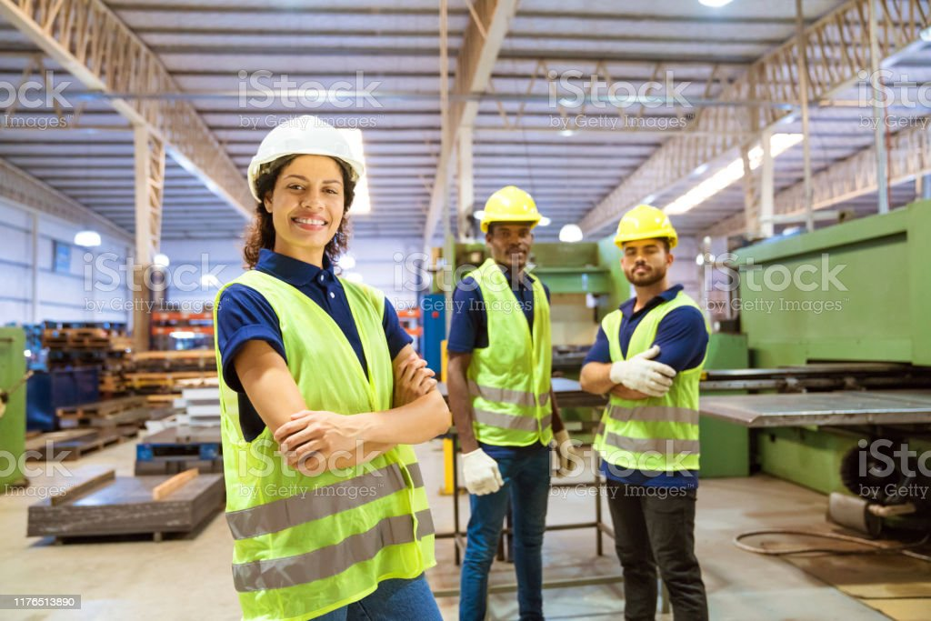 Smiling female engineer against male colleagues Portrait of smiling female engineer standing against colleagues. Expertise are working in industry. They are into manufacturing occupation. 20-24 Years Stock Photo