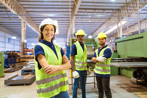 Smiling Female Engineer Against Male Colleagues Stock Photo - Download Image Now