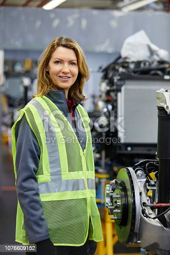 941796726istockphoto Smiling female engineer standing by car part 1076609152