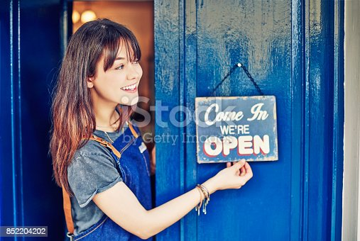 istock Smiling female entrepreneur hanging open sign on deli door 852204202