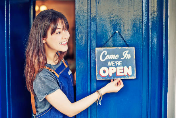 smiling female entrepreneur hanging open sign on deli door - open sign stock pictures, royalty-free photos & images