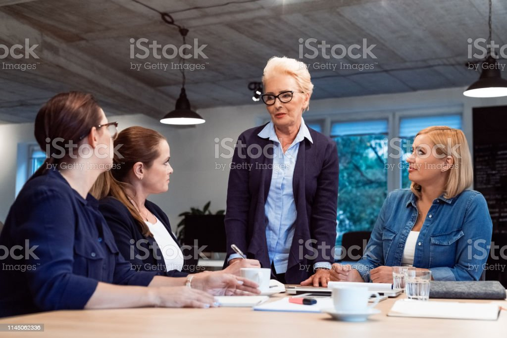 Smiling female entrepreneurs in meeting at office Confident elderly expertise discussing plans with businesswomen. Female professionals are building new strategy together. They are working in start-up office. 35-39 Years Stock Photo