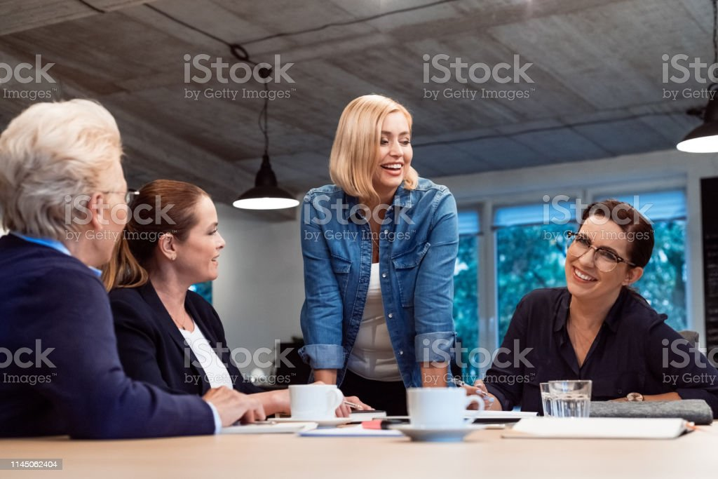 Smiling female entrepreneurs in meeting at office Smiling mature professional discussing with colleagues in meeting. Female entrepreneurs are planning strategy in board room. They are at office. 35-39 Years Stock Photo