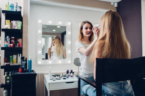 lächelnd weibliche kosmetikerin schminken mit pinsel auf das weibliche modell in stilvollen kosmetikstudio - natürliche make up kurse stock-fotos und bilder