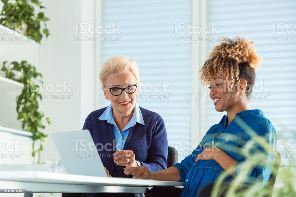 Smiling female executives discussing over laptop Smiling senior businesswoman discussing with pregnant colleague over laptop. Female executives are planning at desk in office. They are running start up business. 35-39 Years Stock Photo