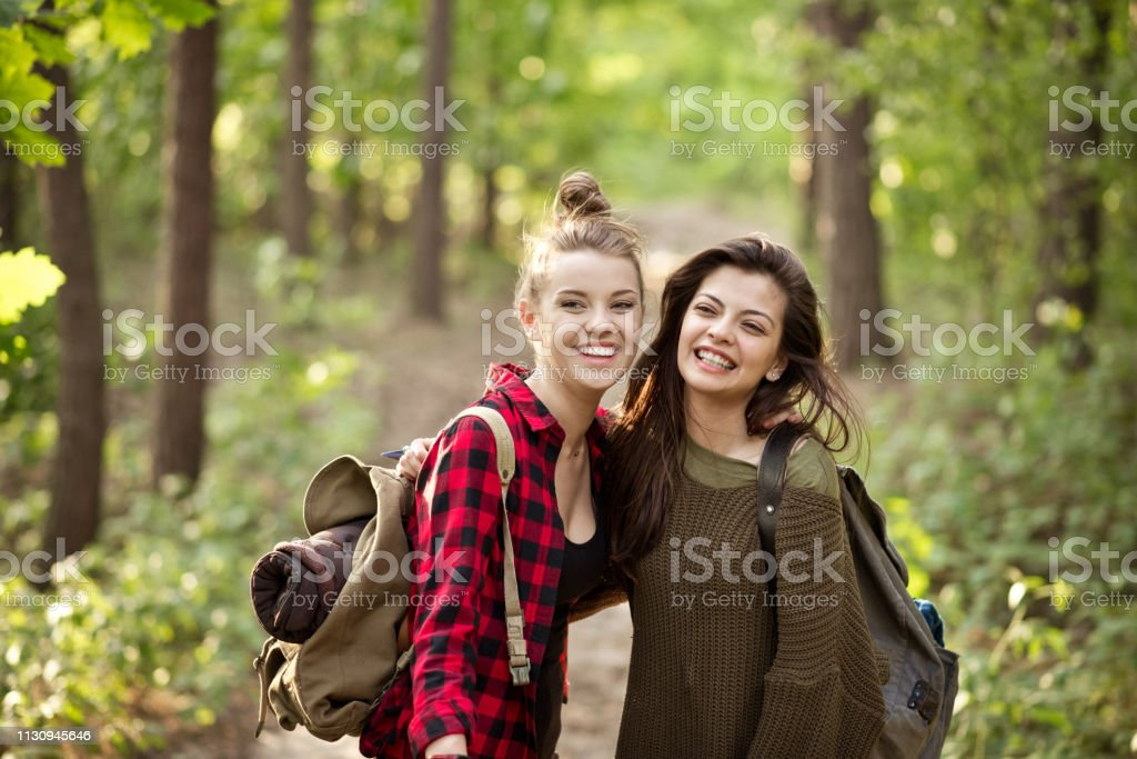 Smiling female explorer with friend in forest Happy beautiful young hikers standing on footpath. Smiling female explorer is with friend. They are spending weekend in forest. 20-24 Years Stock Photo
