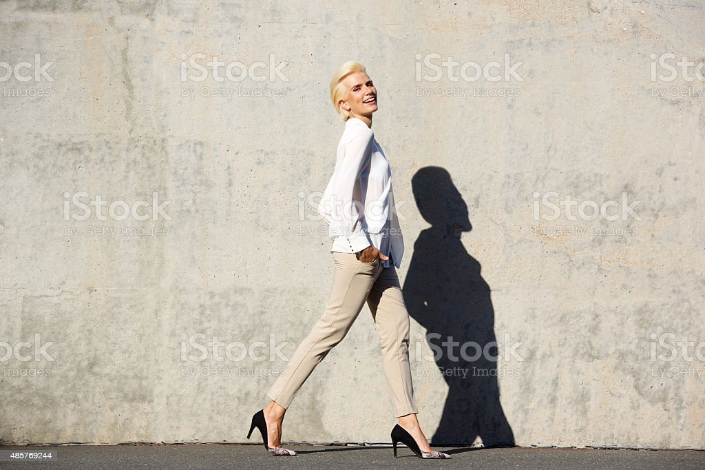 Smiling female fashion model walking stock photo