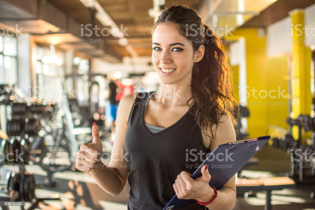 Smiling female fitness instructor with clipboard showing thumb up in gym. stock photo