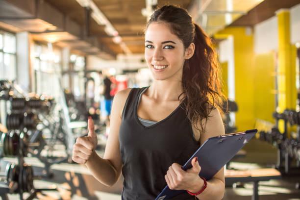 sonriendo instructor de fitness femenino con pulgar de mostrar portapapeles hasta en el gimnasio. - entrenador personal fotografías e imágenes de stock