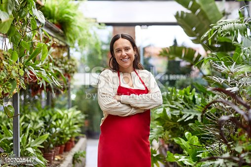 Portrait of confident female florist with arms crossed. Smiling woman is standing in greenhouse. She is working in garden center.