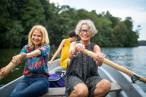 Smiling female friends rowing boat in lake. Mature women are enjoying boating in forest. They are on vacations.