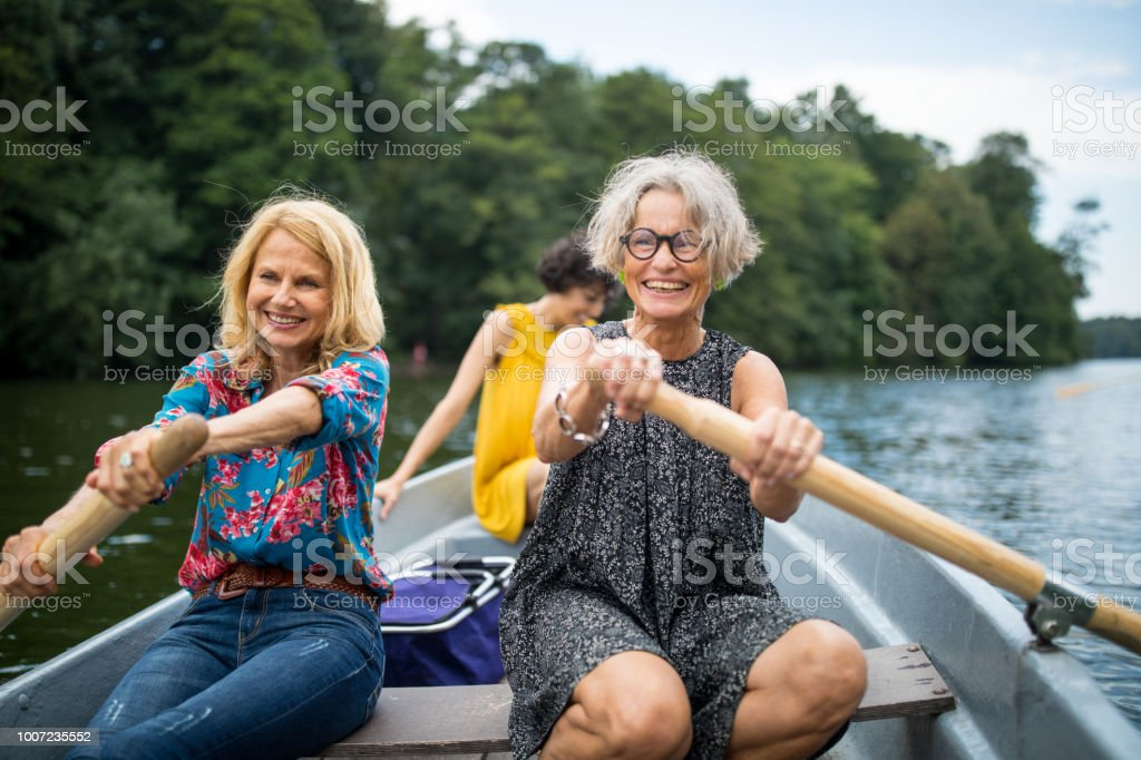 Smiling female friends rowing boat in lake stock photo
