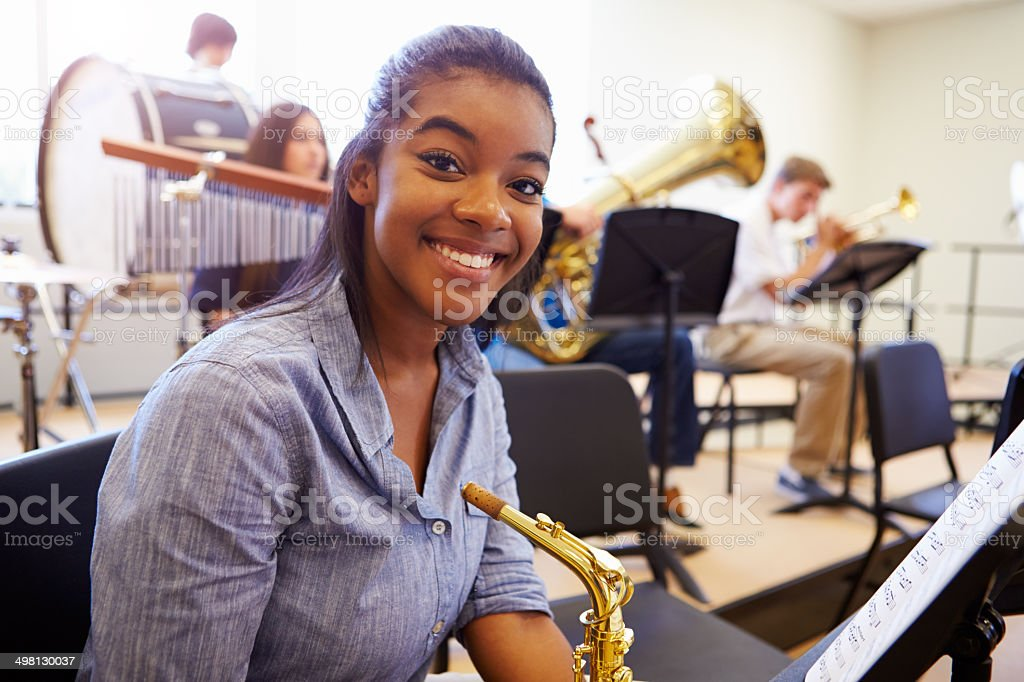 Smiling female high school pupil with saxophone stock photo