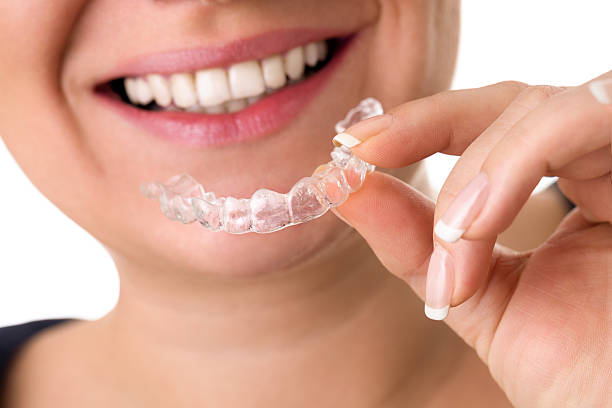 smiling female holding invisible teeth braces stock photo