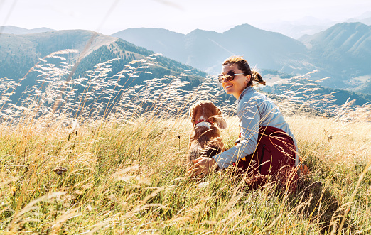 Smiling female hugs her beagle dog resting as they walking in mountains together
