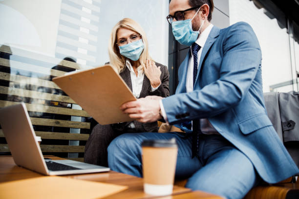 Smiling female in a face mask scrutinizing a contract stock photo