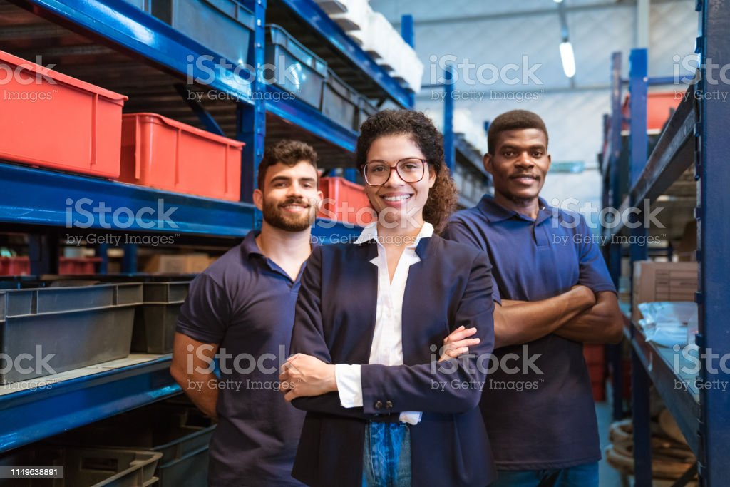Smiling female inspector with workers in factory Portrait of smiling female inspector with workers in factory. Colleagues are standing in storage room. They are working together in warehouse. 20-24 Years Stock Photo
