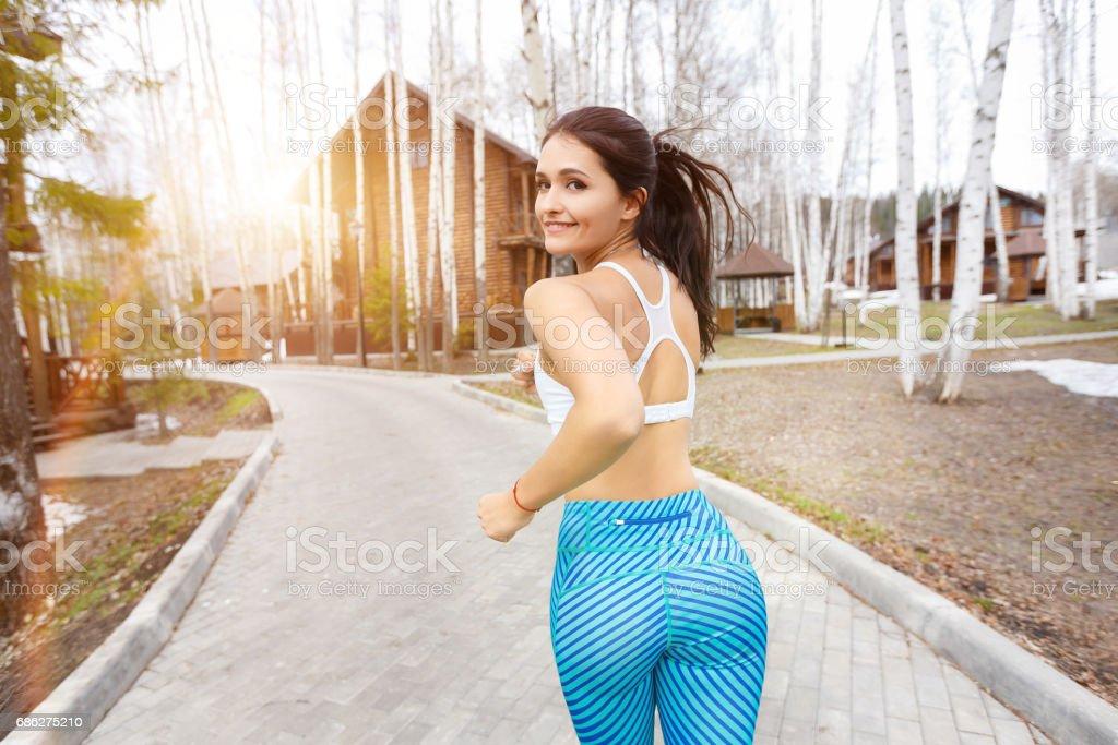 Smiling female jogger training in the morning sunrise stock photo