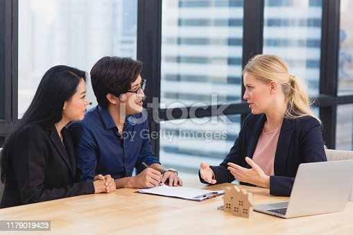 955988522istockphoto Smiling female lawyer or financial adviser show contract and insurance form agreement to multiracial couple customers at office 1179019423