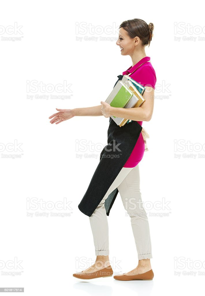 Smiling female librarian holding books and walking stock photo