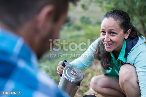 Smiling female looking at male getting ready to pour brewed coffee