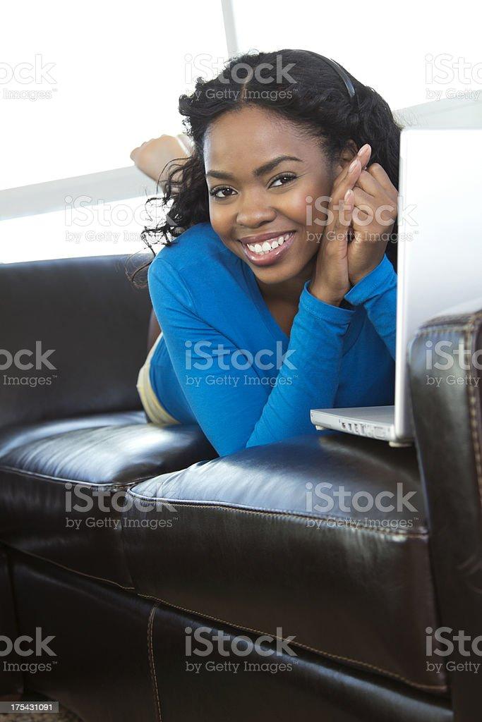 Smiling female lying on sofa stock photo