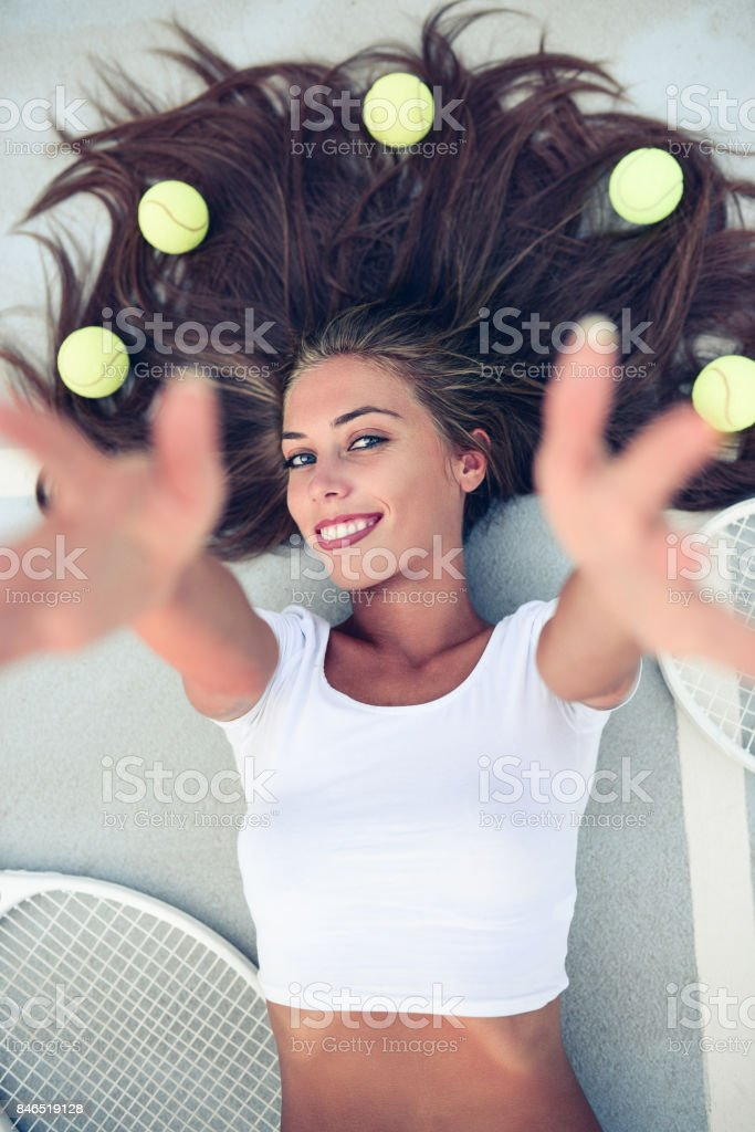 Smiling Female Lying on Tennis Court and Reaching to the Camera stock photo