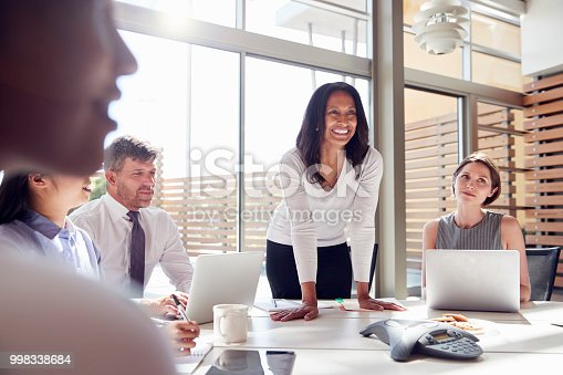 istock Smiling female manager listening to colleagues at a meeting 998338684