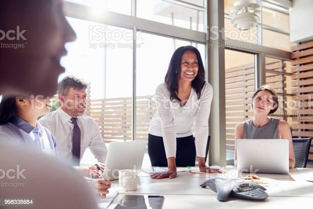 Smiling Female Manager Listening To Colleagues At A Meeting - Fotografias de stock e mais imagens de 20-29 Anos