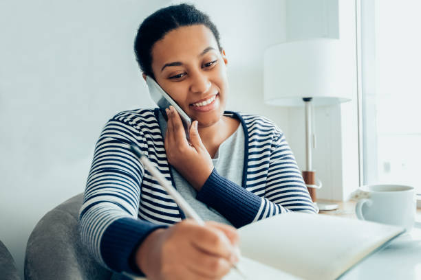 Smiling female manager talking to client on phone_tone stock photo