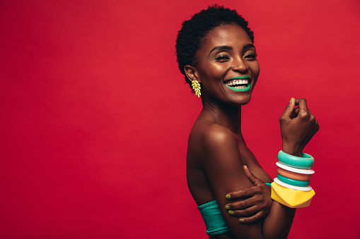 Beautiful young african woman with vivid makeup against red background. Smiling female model wearing artistic makeup looking at camera.