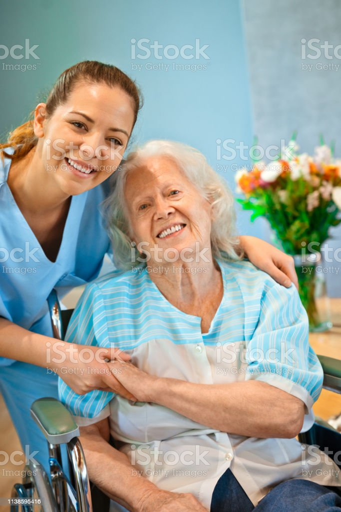 Portrait of smiling healthcare worker holding hands of disabled...