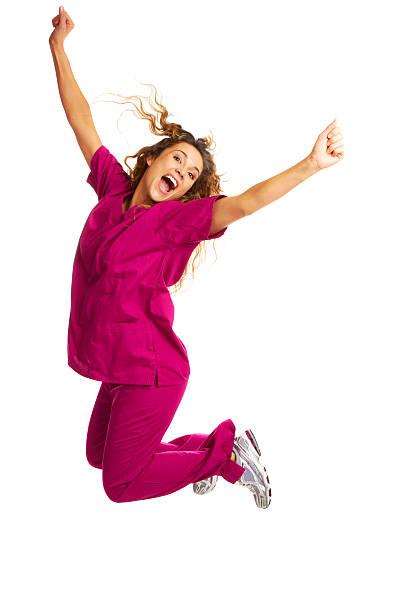 Smiling Female Nurse Throwing Apple Over White Background stock photo
