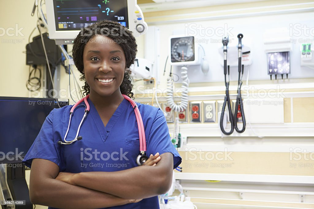 Smiling female nurse with arms folded at a medical facility stock photo
