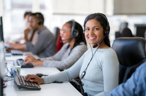 Smiling female operator working in call center Portrait of smiling businesswoman wearing headset while using computer. Confident female operator is working with colleagues at desk. They are in call center. call centre photos stock pictures, royalty-free photos & images