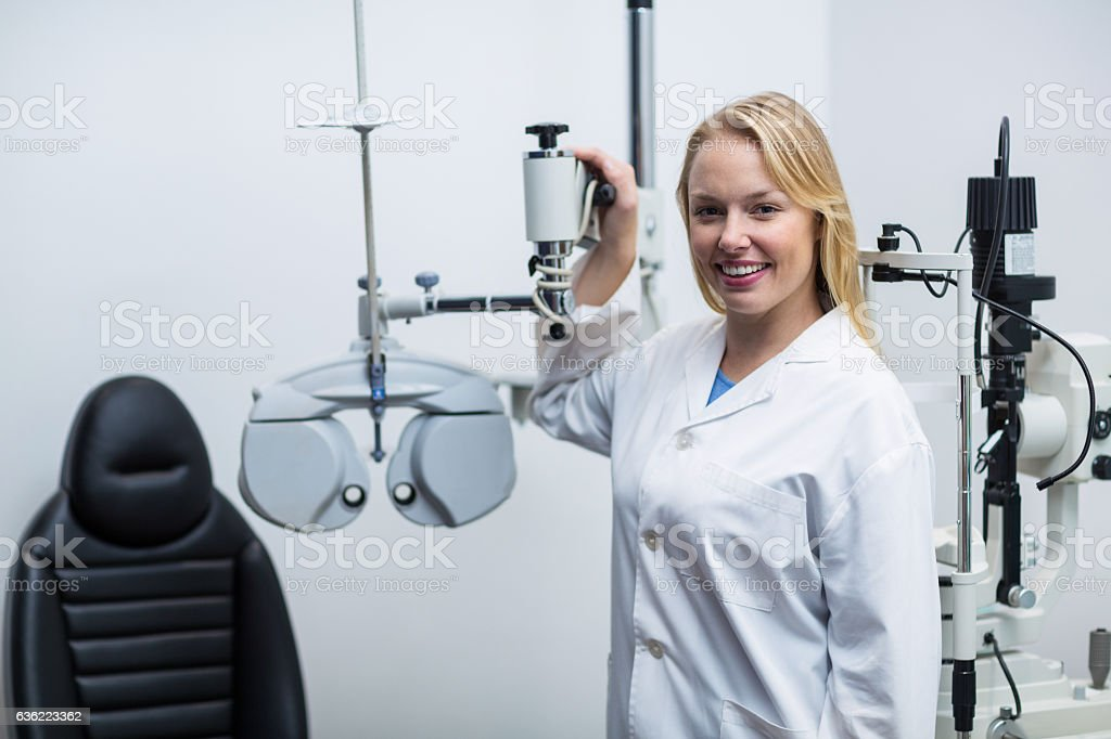 Smiling female optometrist standing near phoropter stock photo