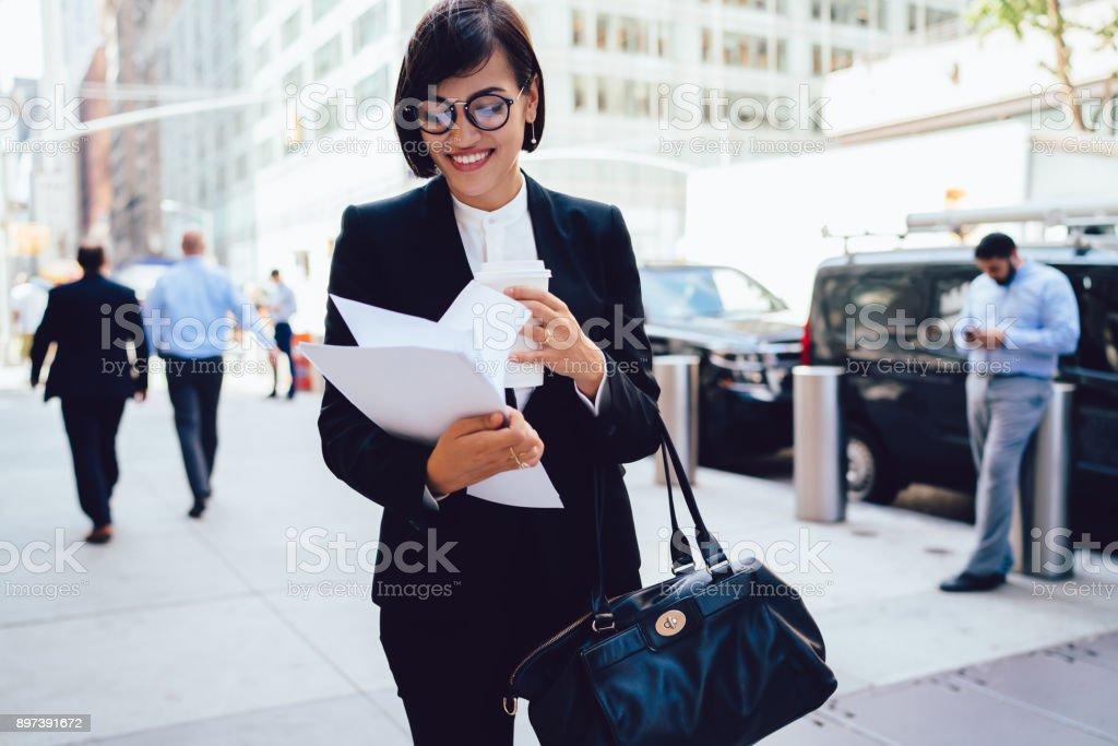 d762a438c Sorrindo mulher proprietária verificando documentos em pé com café para ir  ao ar livre e saco