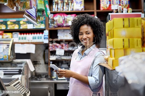 Portrait of confident female owner holding smart phone. Smiling young cashier is standing by checkout. She is working at illuminated store.