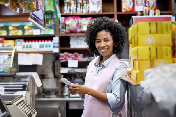 Lächelnde Besitzerin mit Smartphone im Laden – Foto