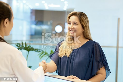 Pretty smiling young Asian woman shaking hand of doctor standing at reception