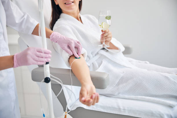 Smiling female patient undergoing intravenous vitamin therapy stock photo