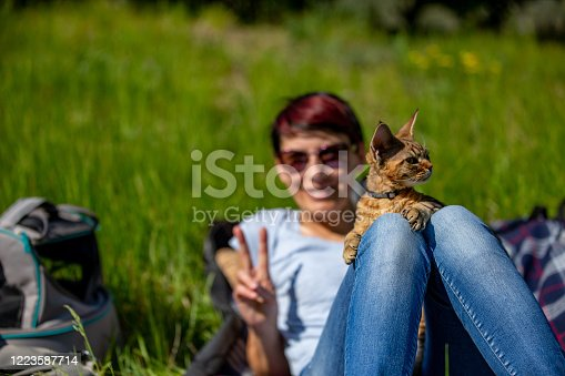 Smiling Female Pet Owner Showing Peace Sign Gesture While Relaxing on Meadow With Her Cat.