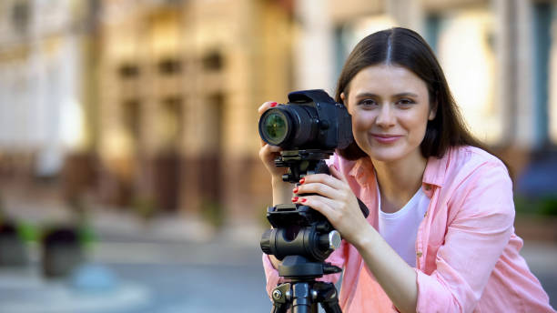 Smiling female photographer focusing camera objective on street photo picture id1183382752?b=1&k=6&m=1183382752&s=612x612&w=0&h=zvwrnwnky2ra 8kkzdygkvrerari6b2wdzqdmj s2a8=