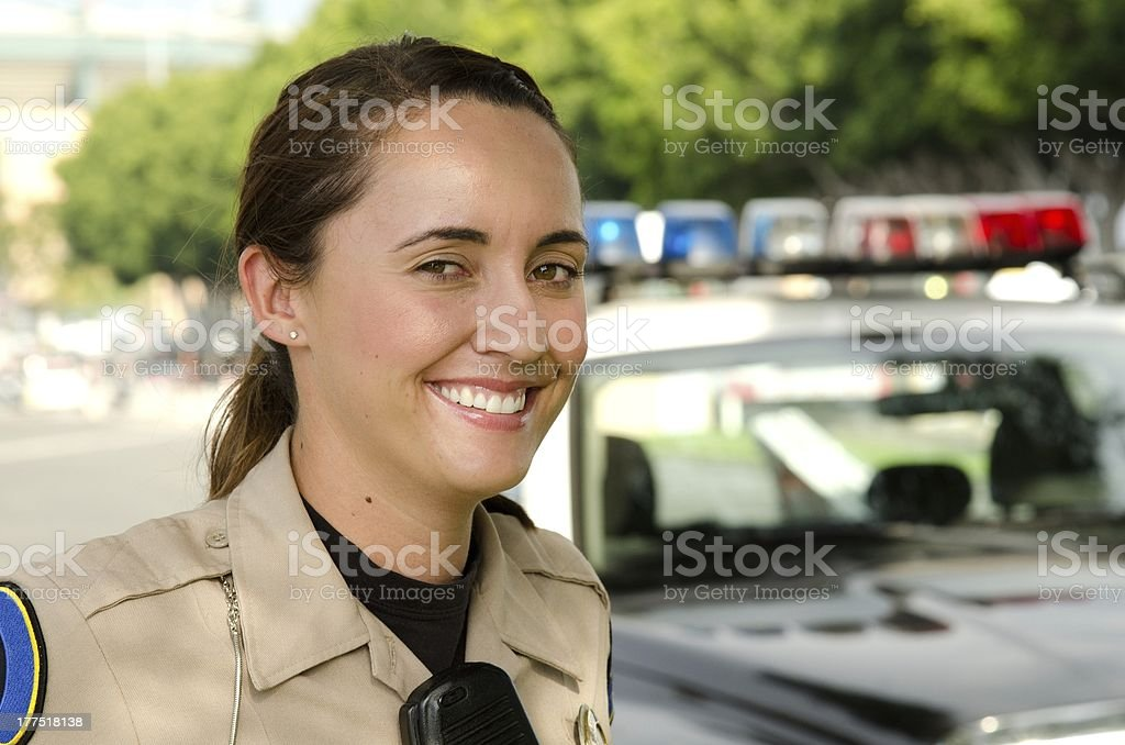 A smiling female police officer with police car in the back stock photo
