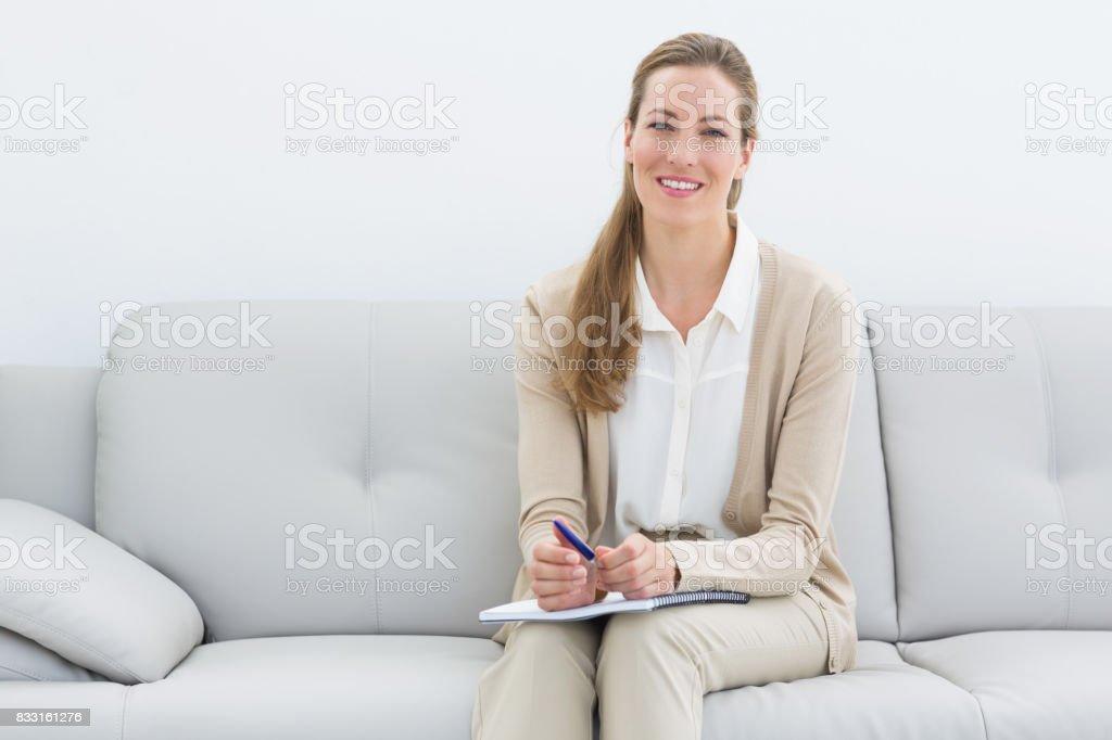 Smiling female psychologist sitting on sofa stock photo